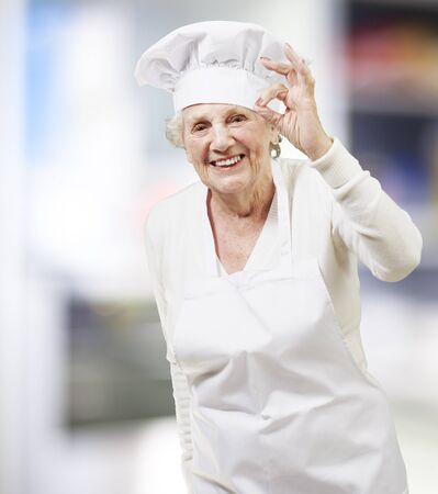 senior woman cook doing an excellent symbol, indoor photo