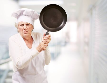 aprons: Cook senior woman angry trying to hit with pan at entrance of modern building