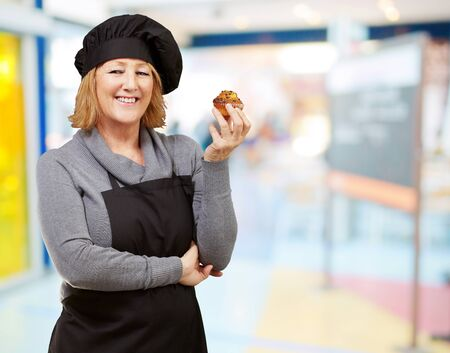 portrait of middle aged cook woman holding a homemade muffin indoor photo