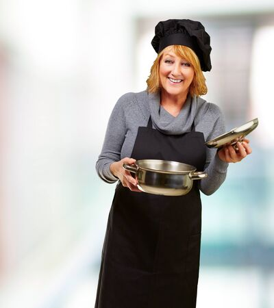 Middle aged cook woman holding a souce pan indoor photo