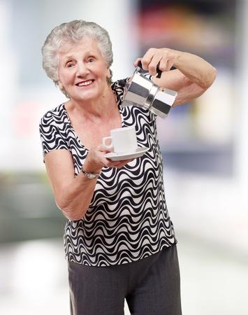 damas antiguas: retrato de una mujer que sirve una vitalidad mayor taza de té en interiores