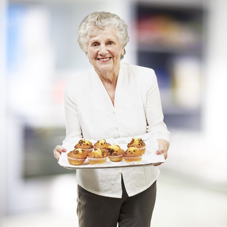 senior woman smiling and holding a tray with muffins, indoor photo