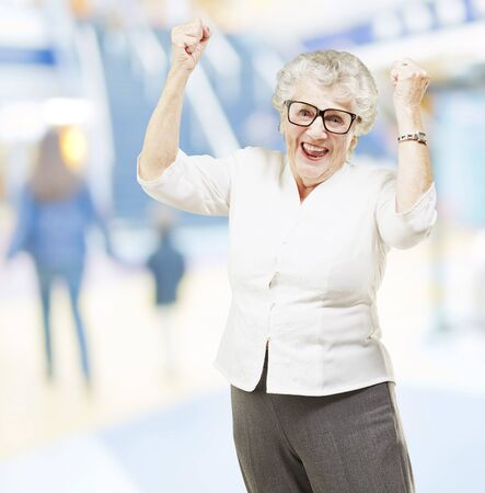 portrait of a happy senior woman doing a victory gesture at mall photo