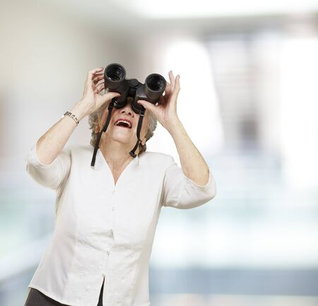 portrait of senior woman looking through a binoculars, indoor photo