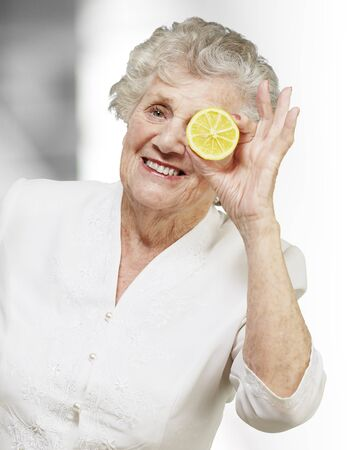 portrait of senior woman with lemon in front of her eye, indoor photo