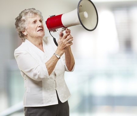 portrait of senior woman holding megaphone against a abstract background photo