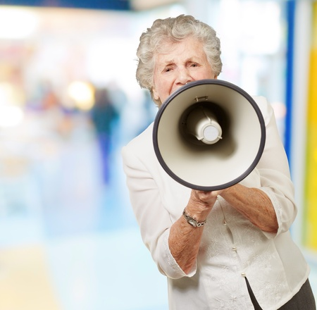 portrait of senior woman screaming with megaphone at crowded place photo