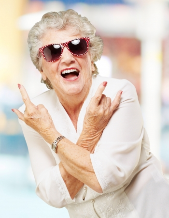 portrait of senior woman smiling and wearing sunglasses against a abstract background Stock Photo