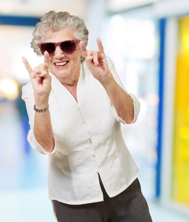 portrait of a happy senior woman doing rock symbol indoor Stock Photo - 14252134