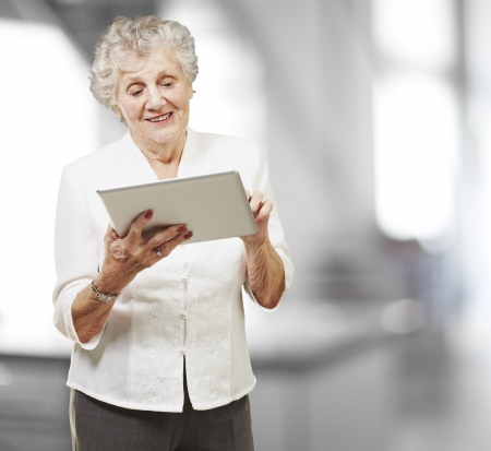 senior computer: portrait of senior woman touching digital tablet, indoor Stock Photo