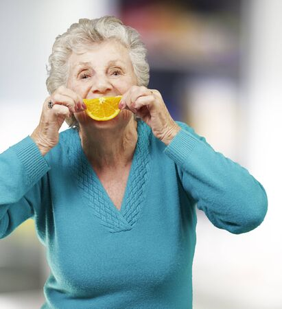 portrait of senior woman holding a orange slice in front of her mouth, indoor Stock Photo - 14252375