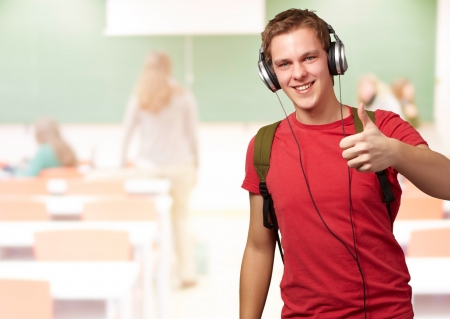 college classroom: portrait of cheerful young student listening music and gesturing good with headphones at classroom