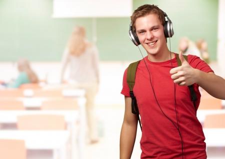 listening to music: retrato de joven estudiante alegre, escuchando m�sica y haciendo un gesto bueno, con los auriculares en el sal�n de clases