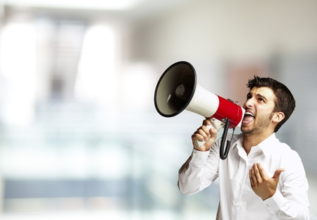 portrait of young man shouting with megaphone against a abstract background photo
