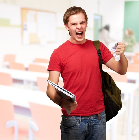 young angry student man roughing a sheet at classroom Stock Photo - 14252251