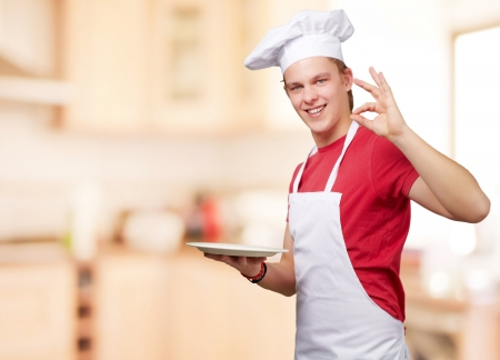 portrait of young cook man at kitchen photo