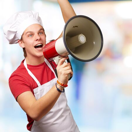 portrait of young cook man shouting with megaphone indoor Stock Photo - 14252053