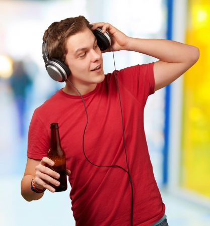 portrait of young man listening music and holding beer indoor Stock Photo - 14252096