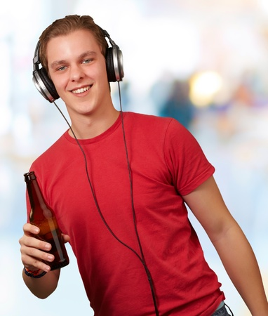 portrait of young man listening music and holding beer indoor photo
