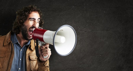 portrait of young man shouting with megaphone against a grunge wall photo