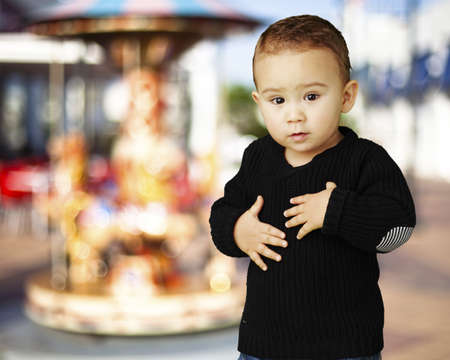adorable boy touching his stomach against a carousel background photo