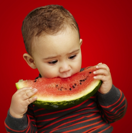 adorable boy eating a watermelon slice against a red background photo