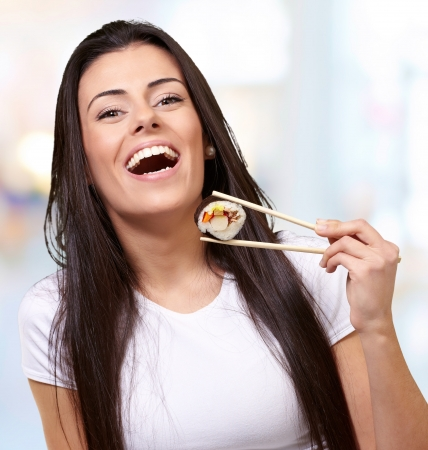 portrait of young woman holding sushi indoor photo