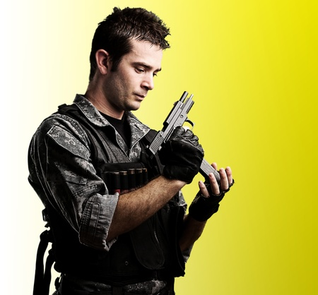 portrait of young soldier reloaing his gun against a yellow background photo