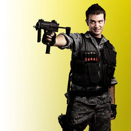 portrait of young soldier smiling with a rifle against a yellow background photo