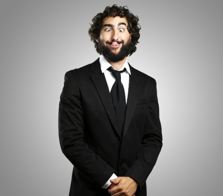 portrait of young business man showing the tongue over grey background photo