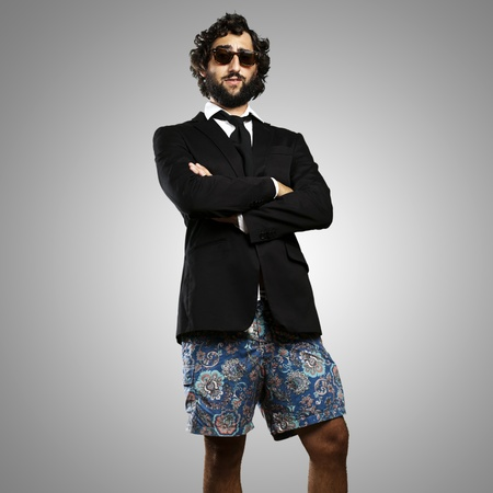 beach wear: portrait of young business man wearing swimsuit against a grey background Stock Photo