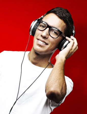 portrait of young man smiling and listening to music against a blue background photo