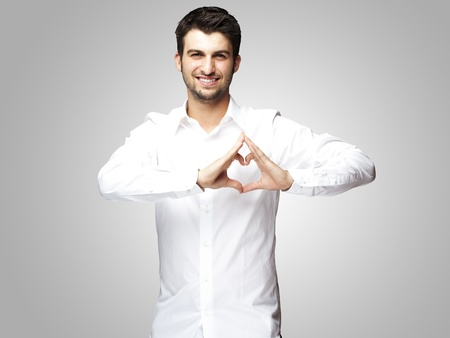 portrait of young man doing heart gesture against a grey background photo