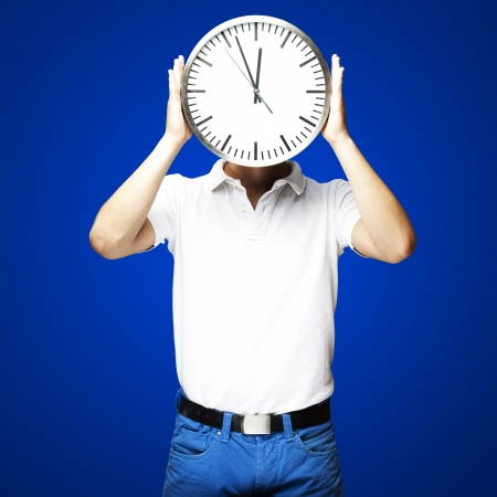 portrait of man holding clock over blue background photo