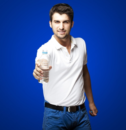 portrait of a handsome young man offering a water bottle over blue background photo