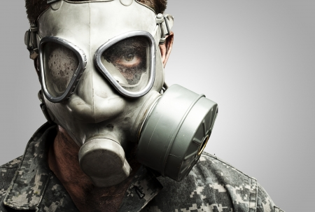 portrait of young soldier wearing gas mask against a grey background photo