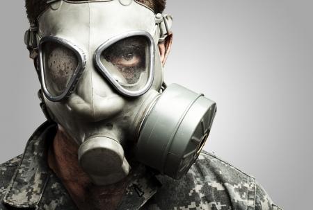 gasmasker: Portret van een jonge soldaat met gasmasker tegen een grijze achtergrond Stockfoto
