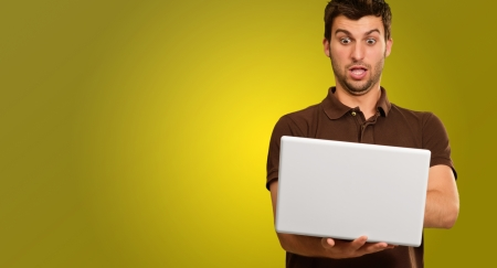 Young Man Using Laptop Isolated On Yellow Background photo