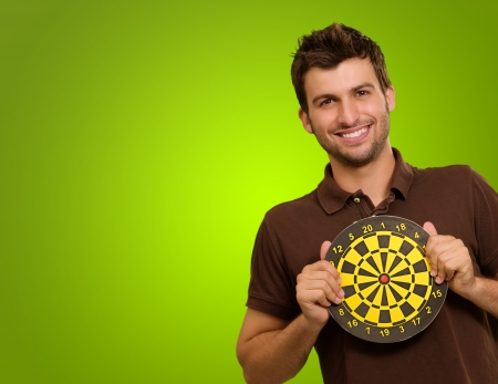 Studio Shot Of Man Holding Bullseye Isolated On A Green Background Stock Photo - 14438879
