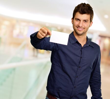 Portrait Of Young Man Holding Blank White Card, Indoor photo