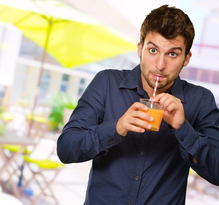 Man Sipping Juice Through Straw, Outdoor photo