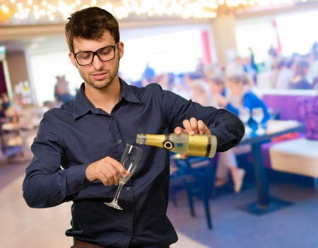 Young Man Pouring Champagne, Indoor photo