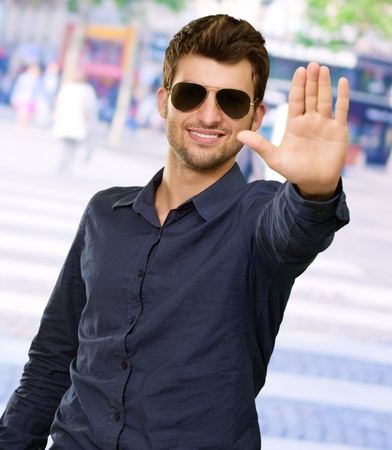 upraised: Portrait Of Young Man Doing Stop Signal, Outdoor