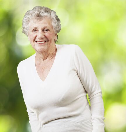 pretty senior woman smiling against a nature background photo