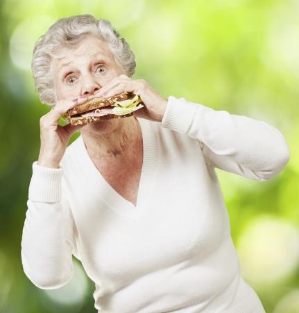 Senior Frau isst ein gesundes Sandwich gegen eine Natur Hintergrund