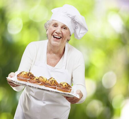 senior woman cook holding a tray with muffins against a nature background photo
