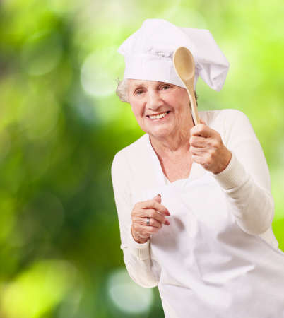 portrait of senior cook woman holding a wooden spoon against a nature background photo