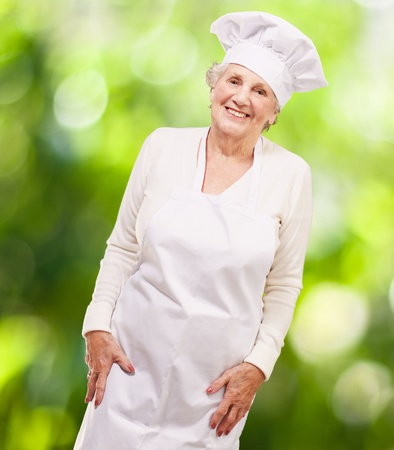 portrait of cook senior woman smiling against a nature background photo