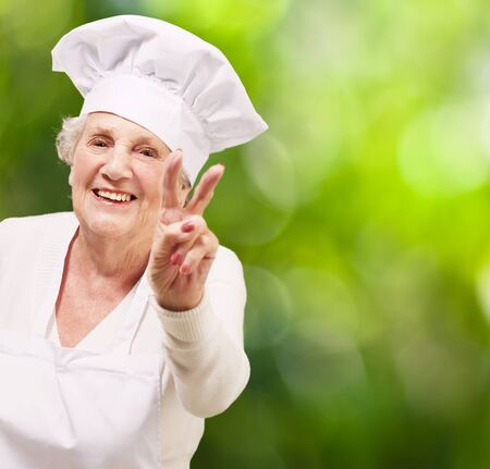 portrait of cook senior woman doing good gesture against a nature background photo