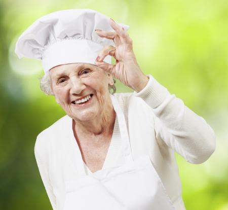 abuela: cocinero mujer mayor haciendo un excelente s�mbolo contra la naturaleza de fondo